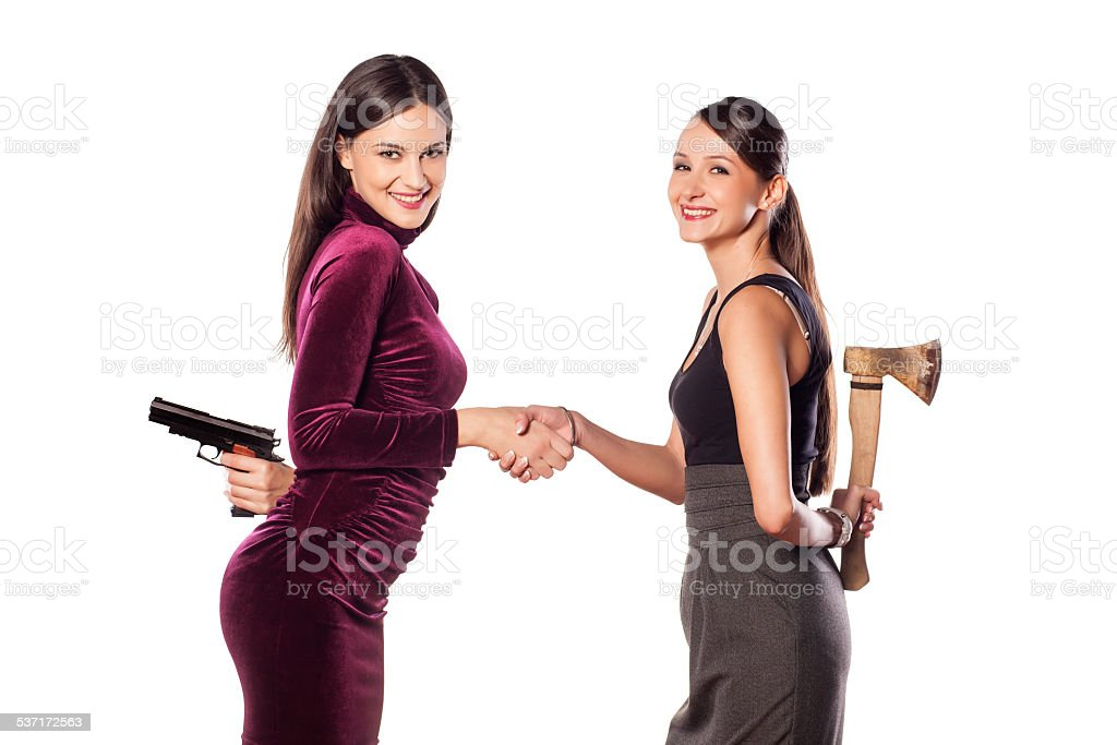 Two young women shake hands warmly with weapons behind stock photo