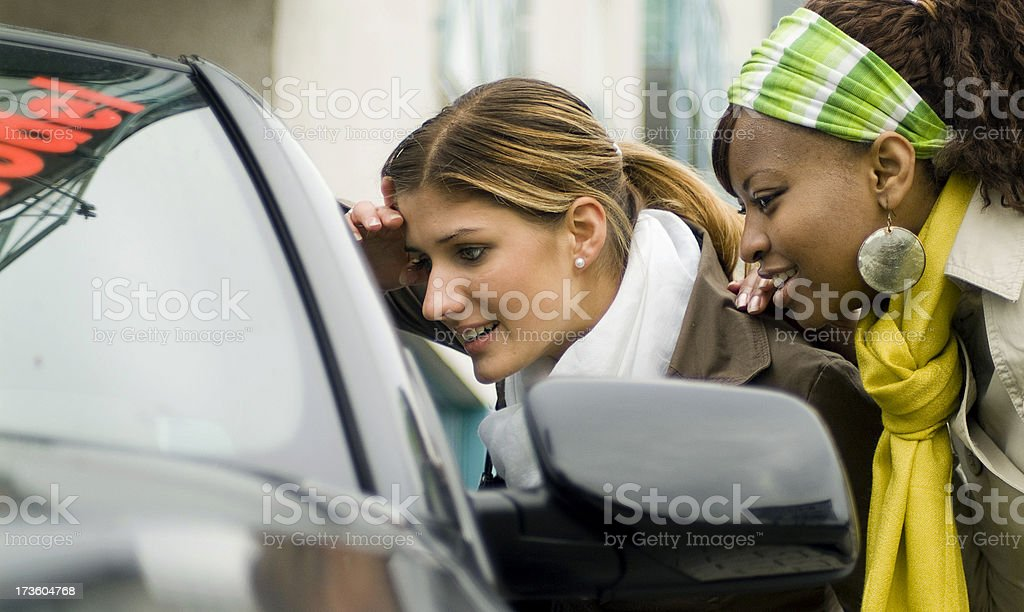 two young women shopping for a new car, looking in window stock photo