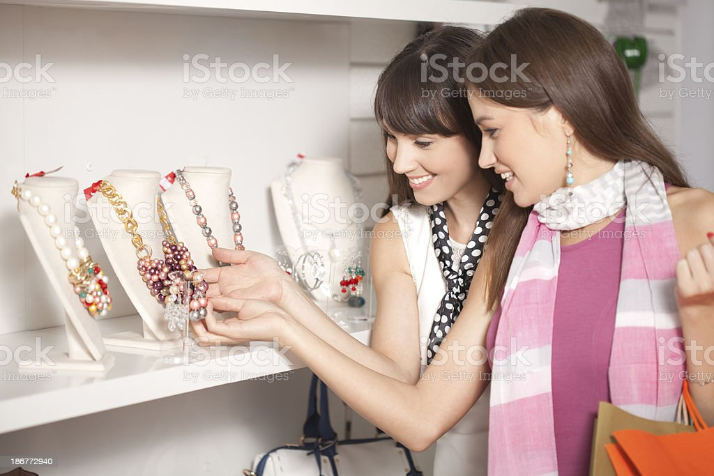 Two young women shopping for jewelry in a store royalty-free stock photo