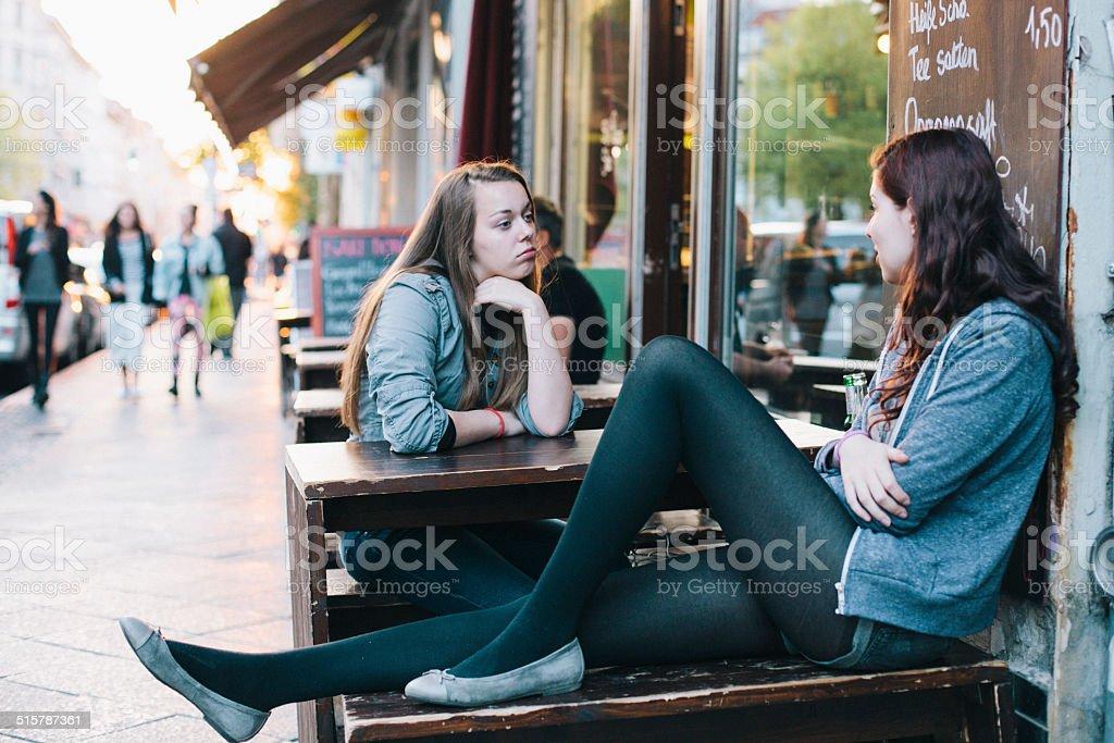 two young women sit in Sidewalk Cafe in Berlin Kreuzberg stock photo