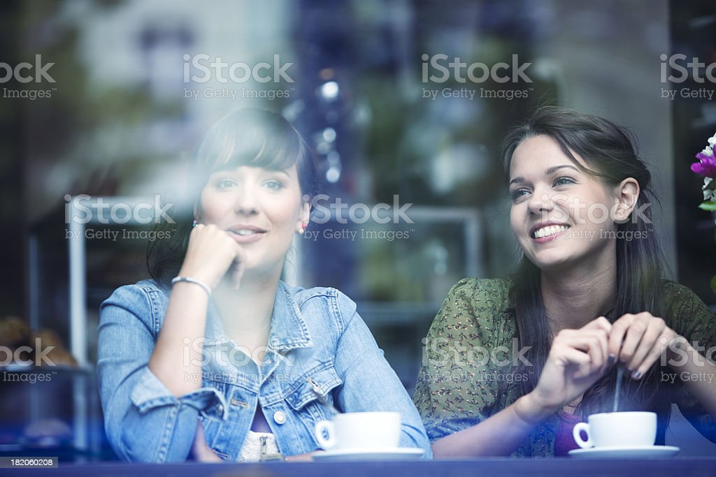 Two Young Women Sitting in Cafe, Smiling, View Through Glass stock photo
