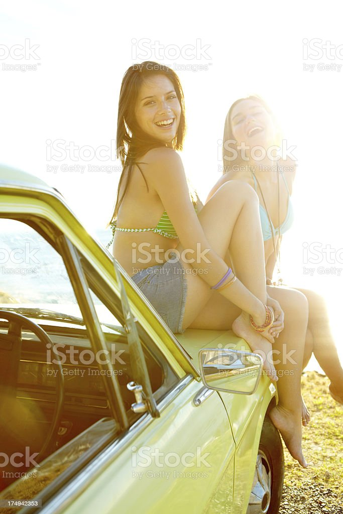 Two young women sitting on car hood at the beach royalty-free stock photo