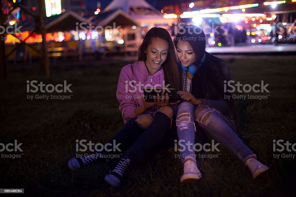 Two young women sitting on grass and using digital tablet stock photo