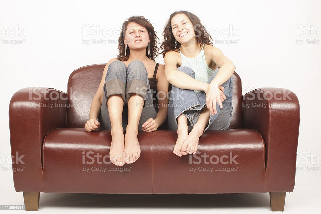 Two young women sitting on sofa and watching tv royalty-free stock photo