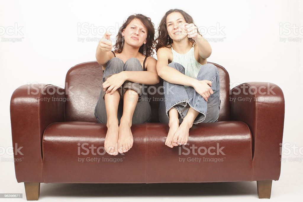 Two young women sitting on sofa watching tv changing chanel royalty-free stock photo
