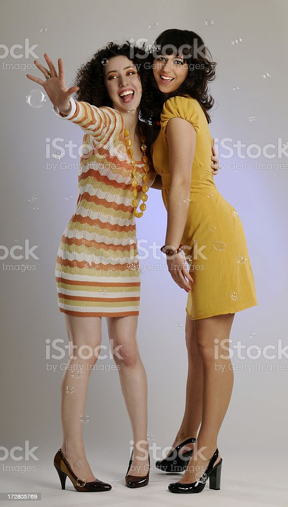 Two Young Women Smiling, Laughing, Having Fun Playing with Bubbles royalty-free stock photo