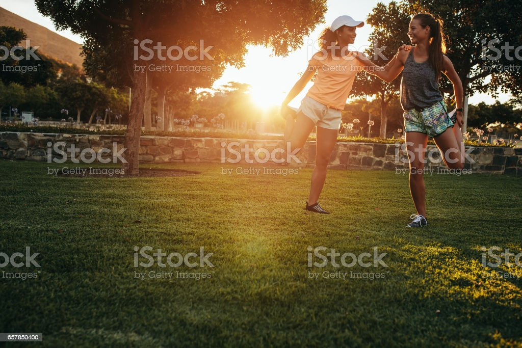 Two young women stretching at park stock photo