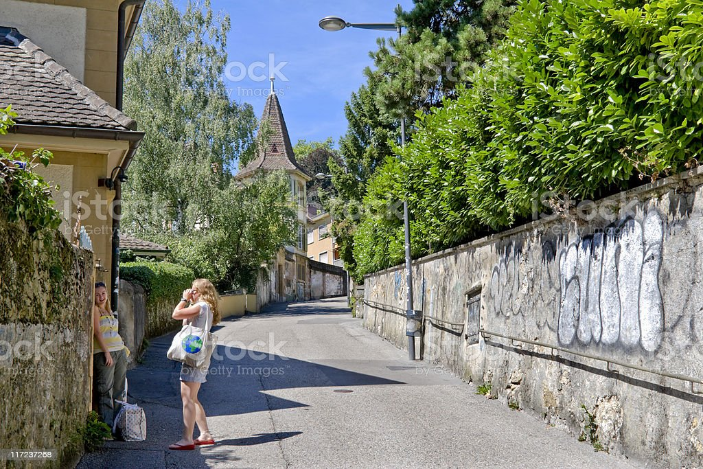 Two Young Women Taking Pictures on a Street in Neuchatel royalty-free stock photo