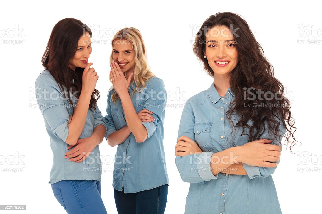 Two young women talking behind their leader's back stock photo