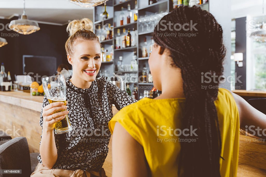 Two young women talking in a pub stock photo