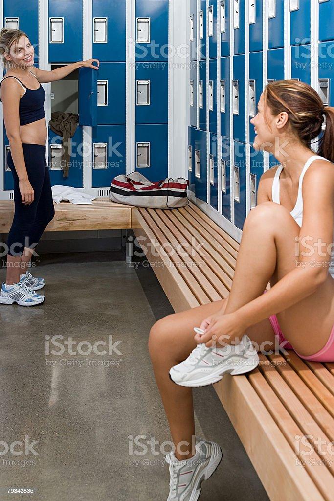 Two young women talking in locker stock photo