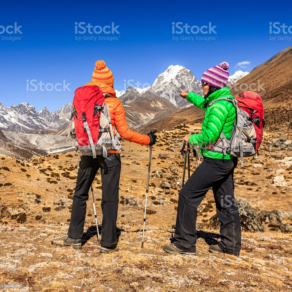 Two young women trekking in Himalayas stock photo