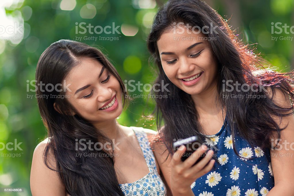 Two young women using a smartphone stock photo