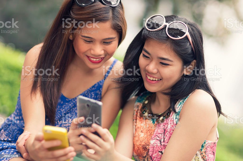 Two young women using their phones together stock photo