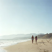 Two young women walking on beach, rear view