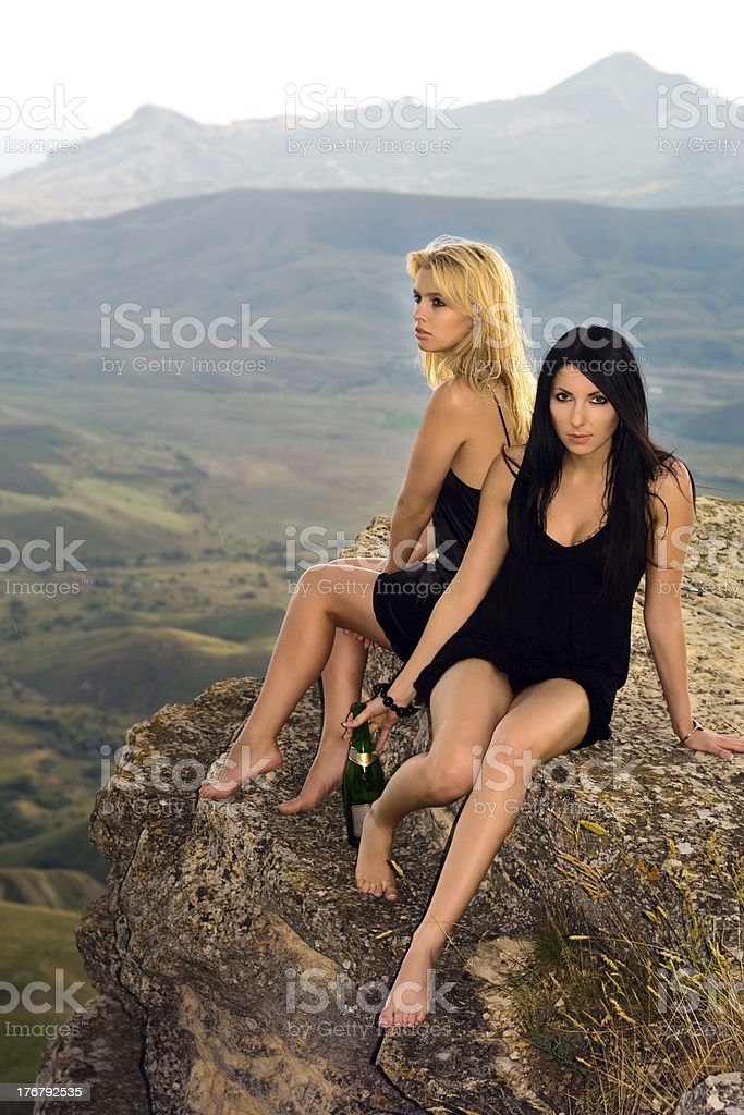 Two young women with a champagne bottle royalty-free stock photo