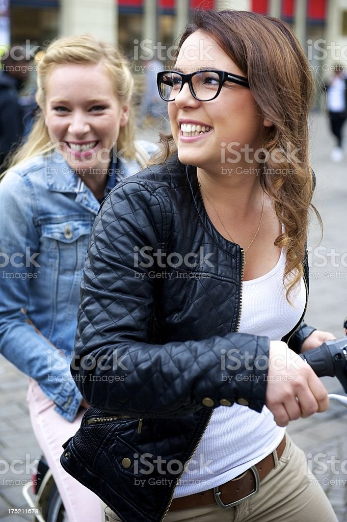 Two young women with bicycle stock photo