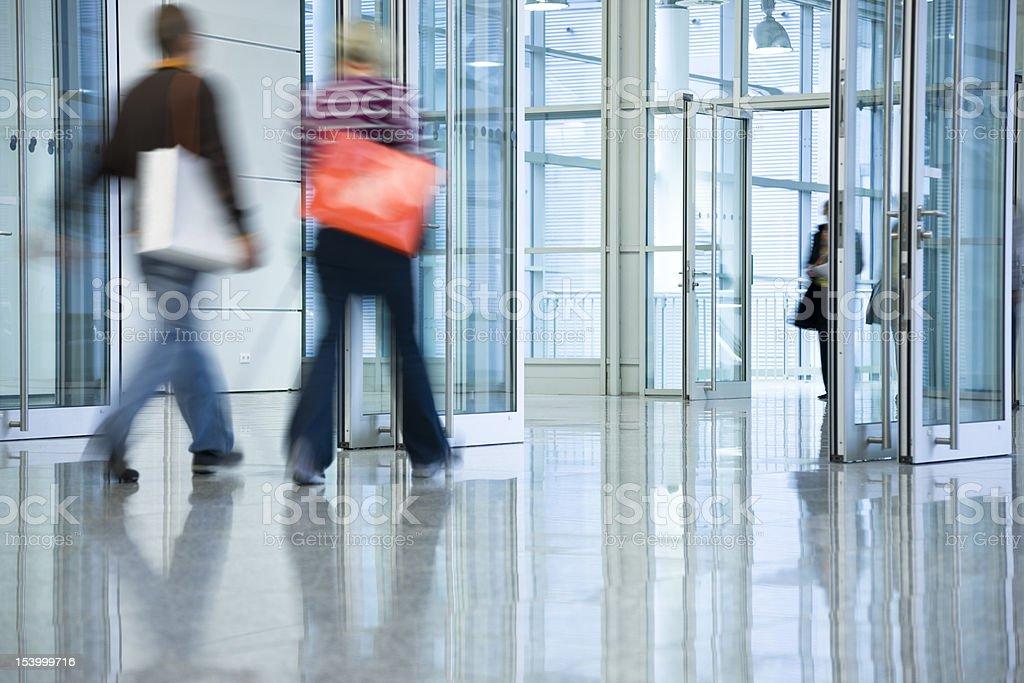 Two Young Women with Shopping Bags Walking Through the Doors stock photo