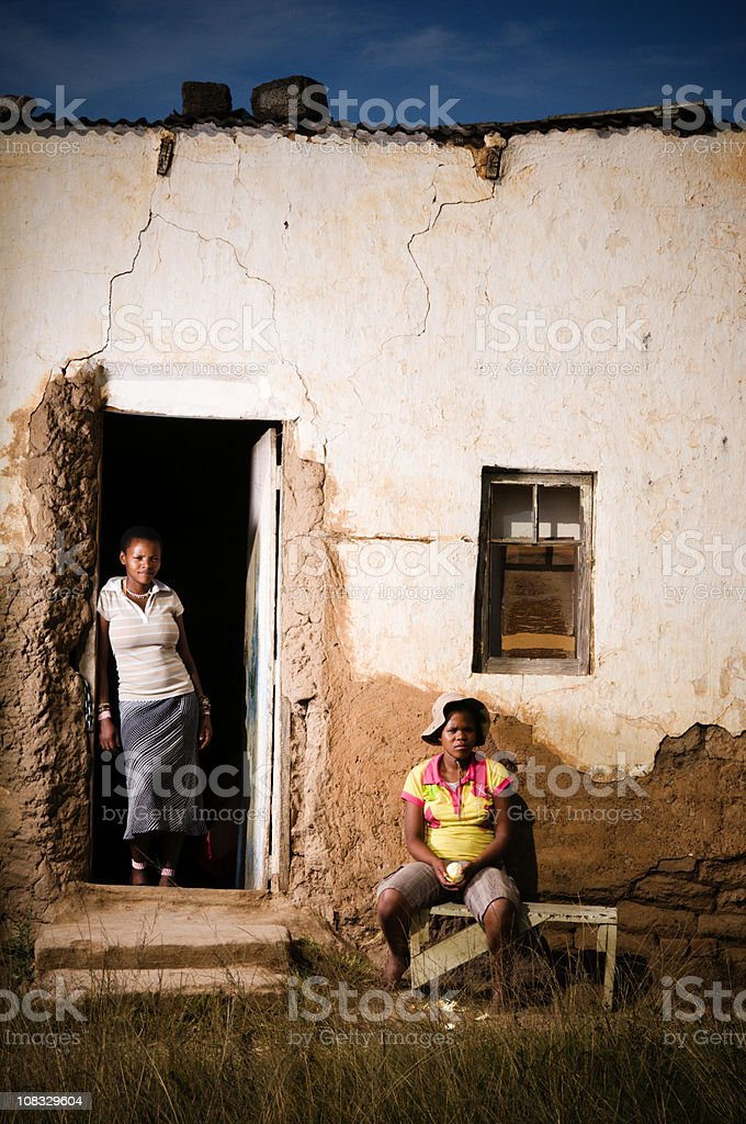Two young Xhosa females in front of rural home royalty-free stock photo