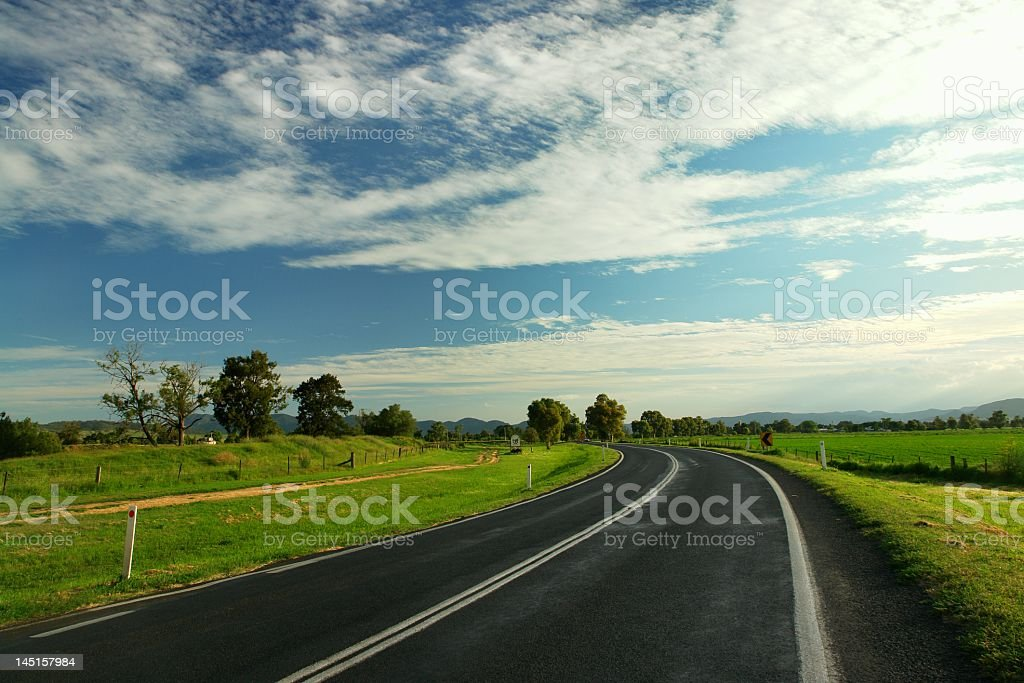 Two-lane paved highway over a grass field with blue sky royalty-free stock photo