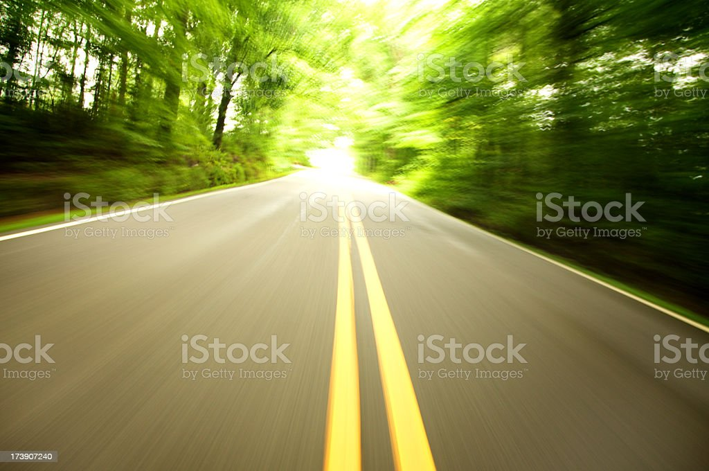 Two-lane paved road with motion-blurred trees royalty-free stock photo