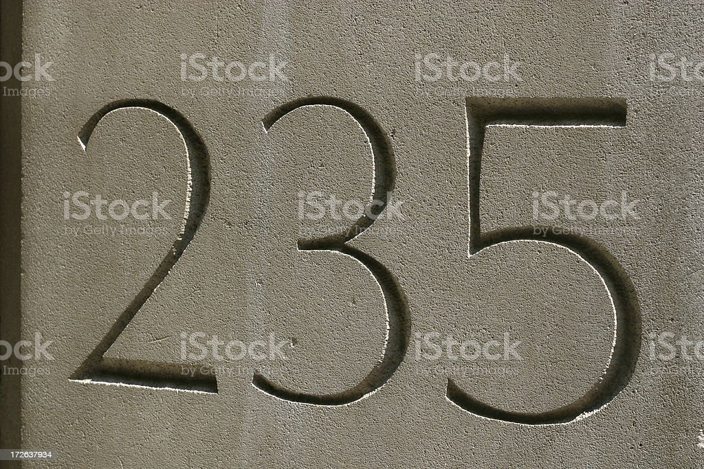TwoThree Five carved in stone stock photo