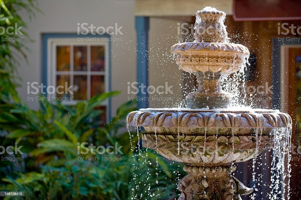 Two-tiered garden fountain flowing with water stock photo
