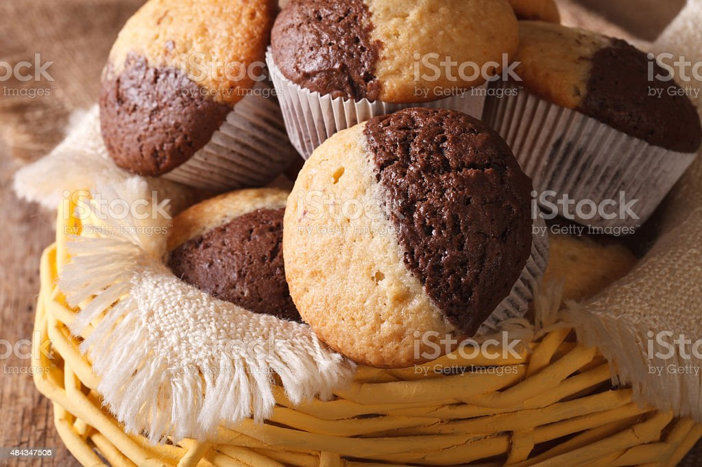 two-tone muffins orange and chocolate closeup in basket stock photo