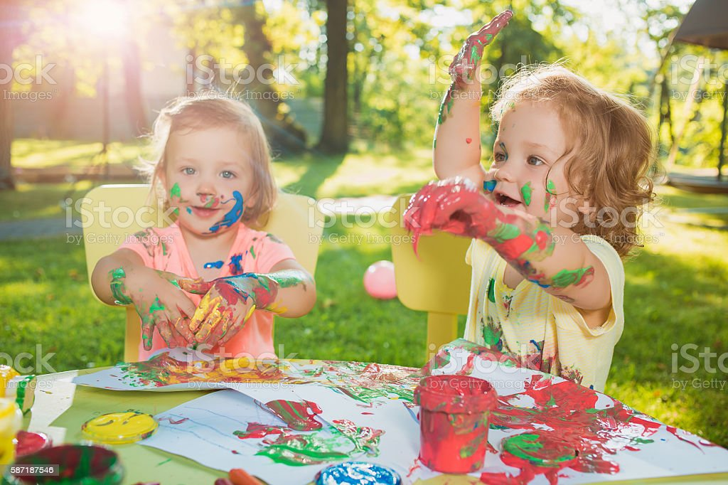 Two-year old girls painting with poster paintings together against stock photo