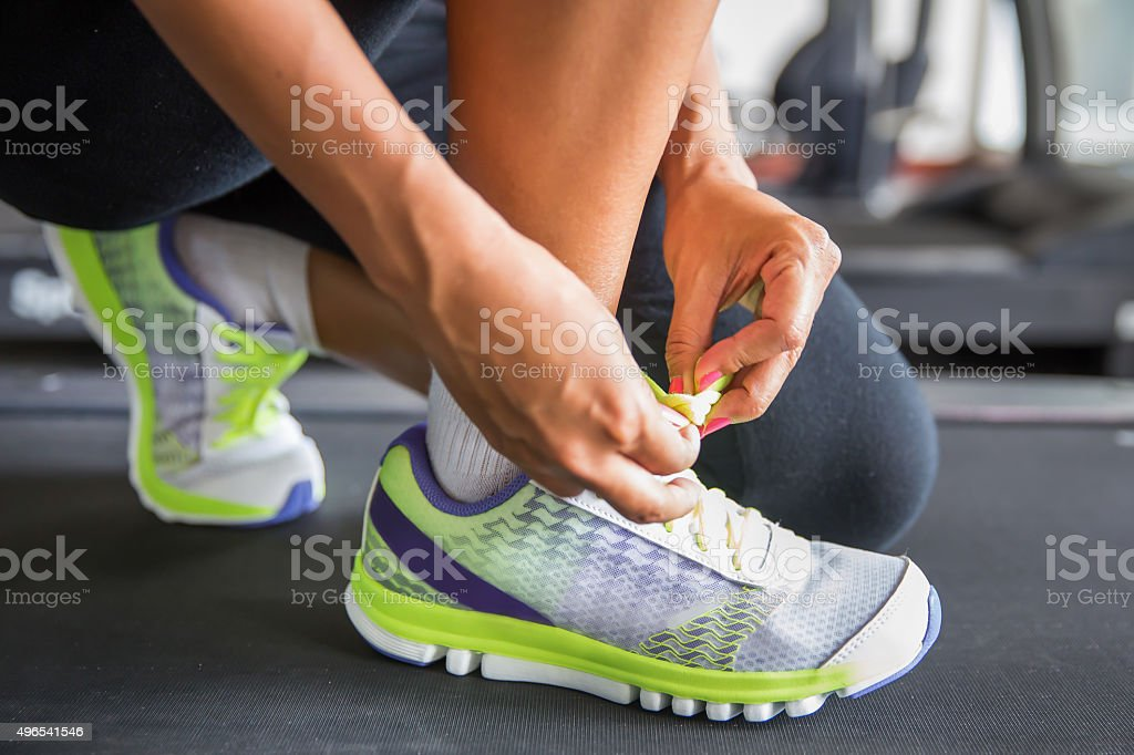 Tying sports shoe at the gym stock photo