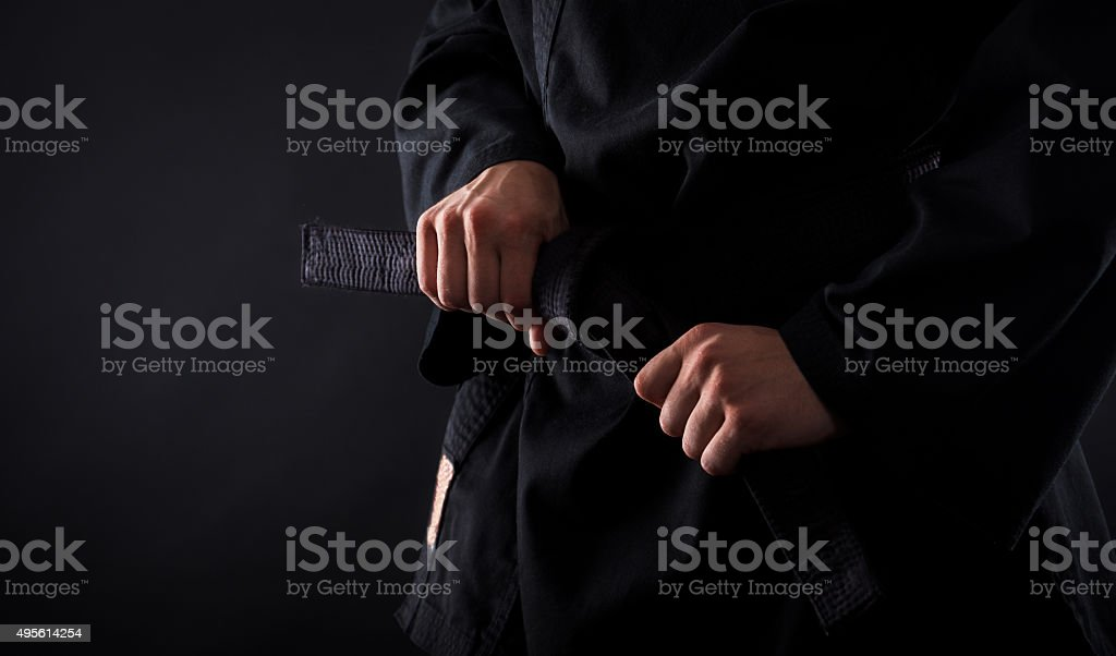 Tying the knot to his black belt stock photo