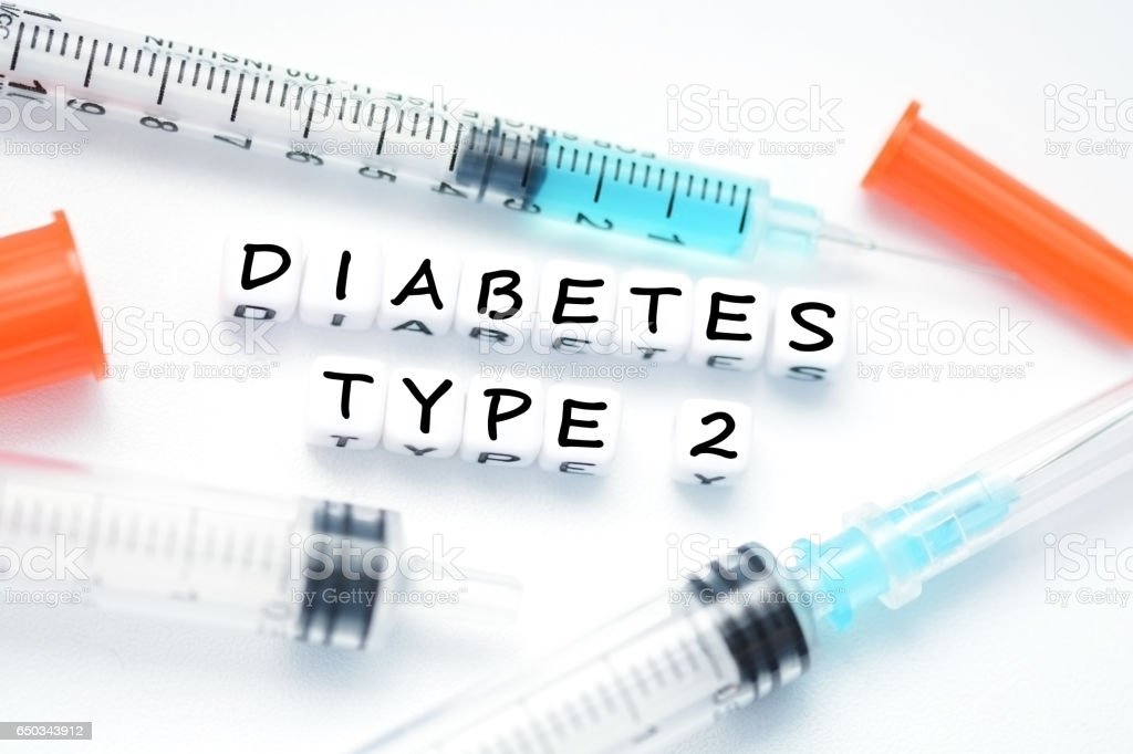 Type 2 diabetes text spelled with plastic letter beads placed next to an insulin syringe stock photo