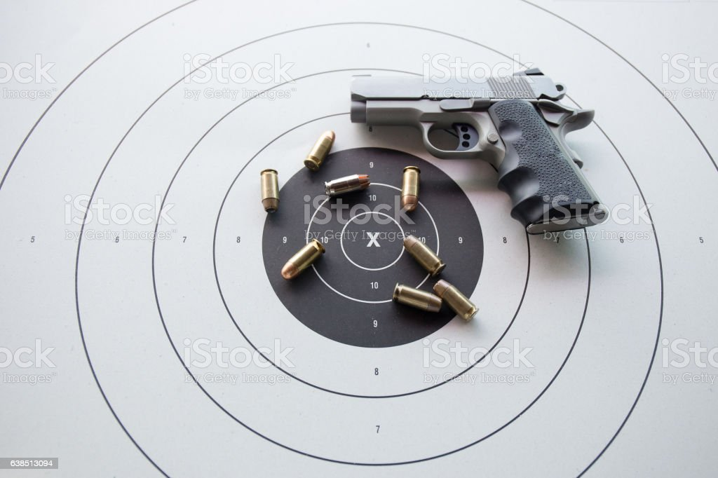type of .45 bullets on  bullseye target with blurred pistol stock photo