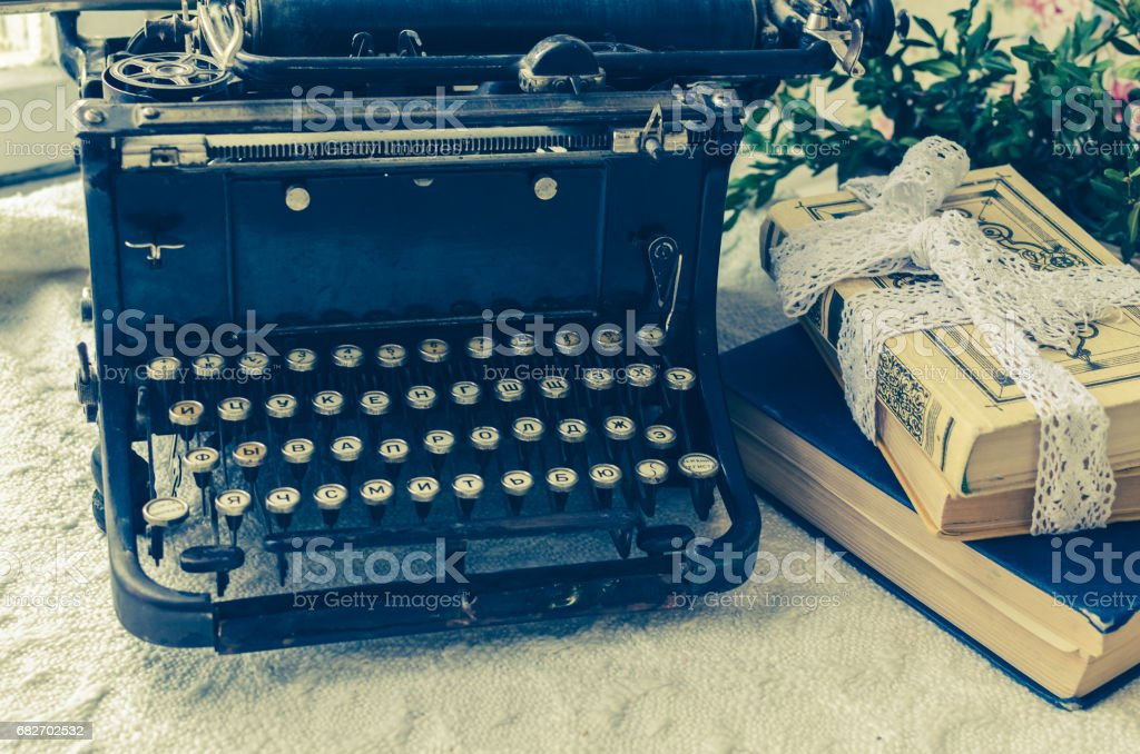 Typewriter and books on the table stock photo