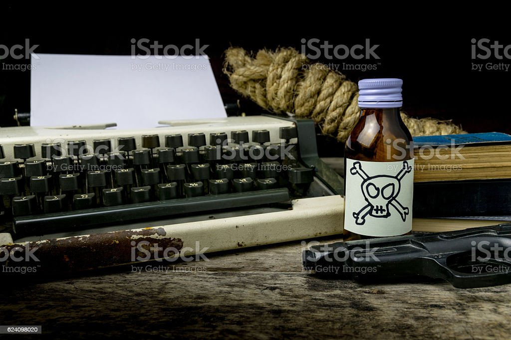 Typewriter with paper page and poison and gun. Concept stock photo
