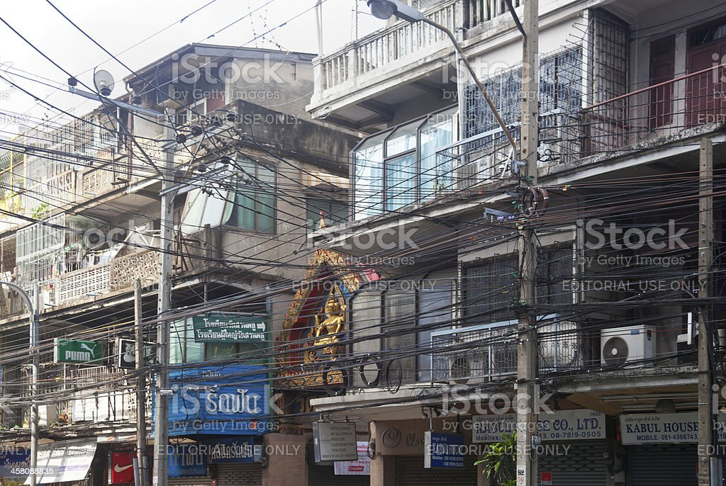 Typical Bangkok street. Old houses and tangle of electric cables. stock photo
