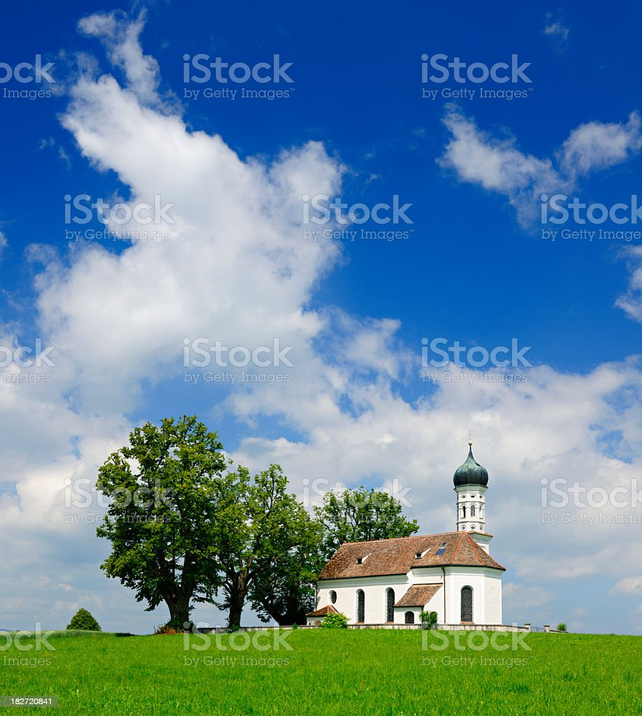 Typical Bavarian Church on Green Meadow under White-Blue Sky royalty-free stock photo