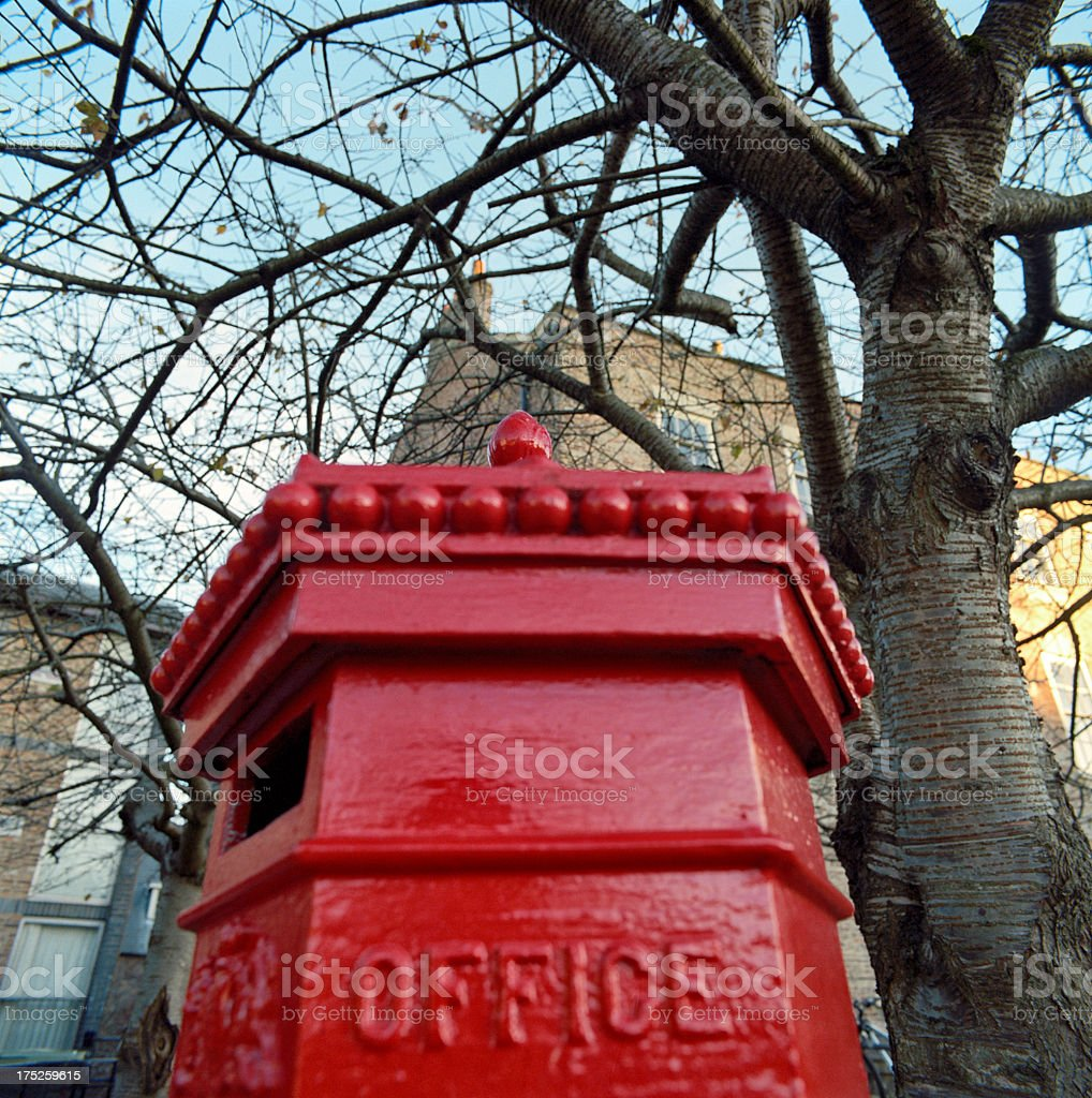 Typical British postbox in traditional English setting royalty-free stock photo