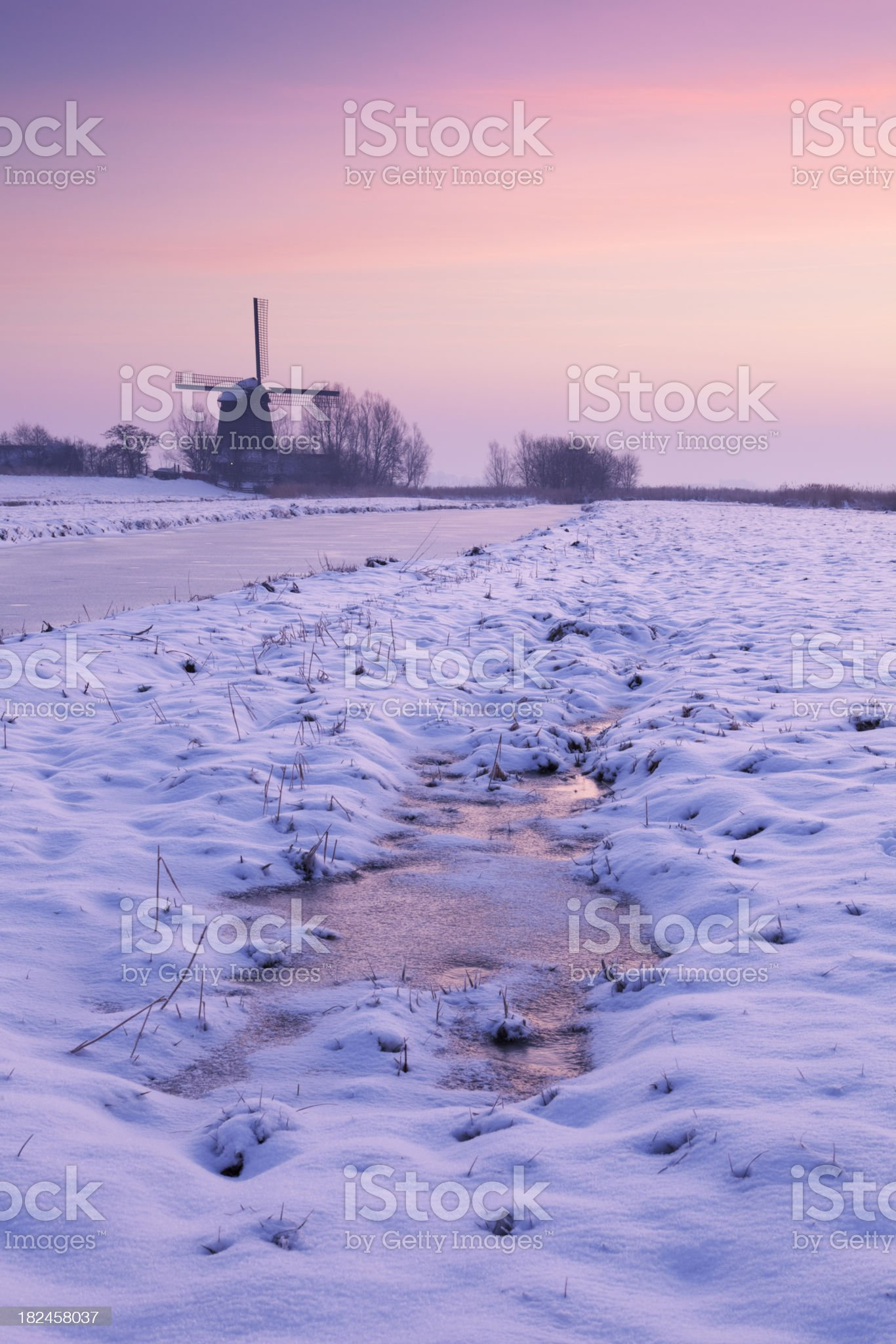 Typical Dutch landscape with windmill in winter at sunrise royalty-free stock photo
