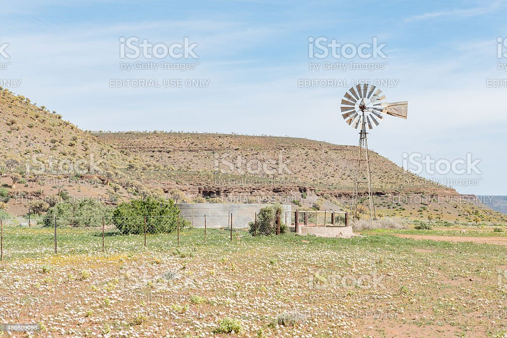 Typical farm scene with water pumping windmill and dam stock photo