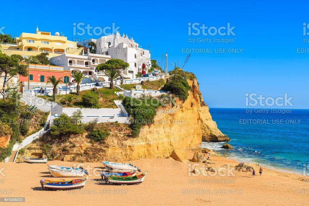 CARVOEIRO BEACH, PORTUGAL - MAY 11, 2015: typical fishing boats on beach in Carvoeiro coastal village. Carvoeiro is popular holiday tourist destination on Algarve coast. stock photo