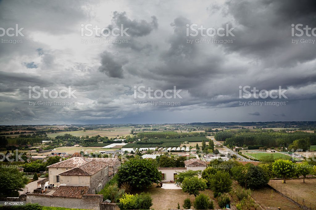 typical french village and countryside with storm clouds stock photo