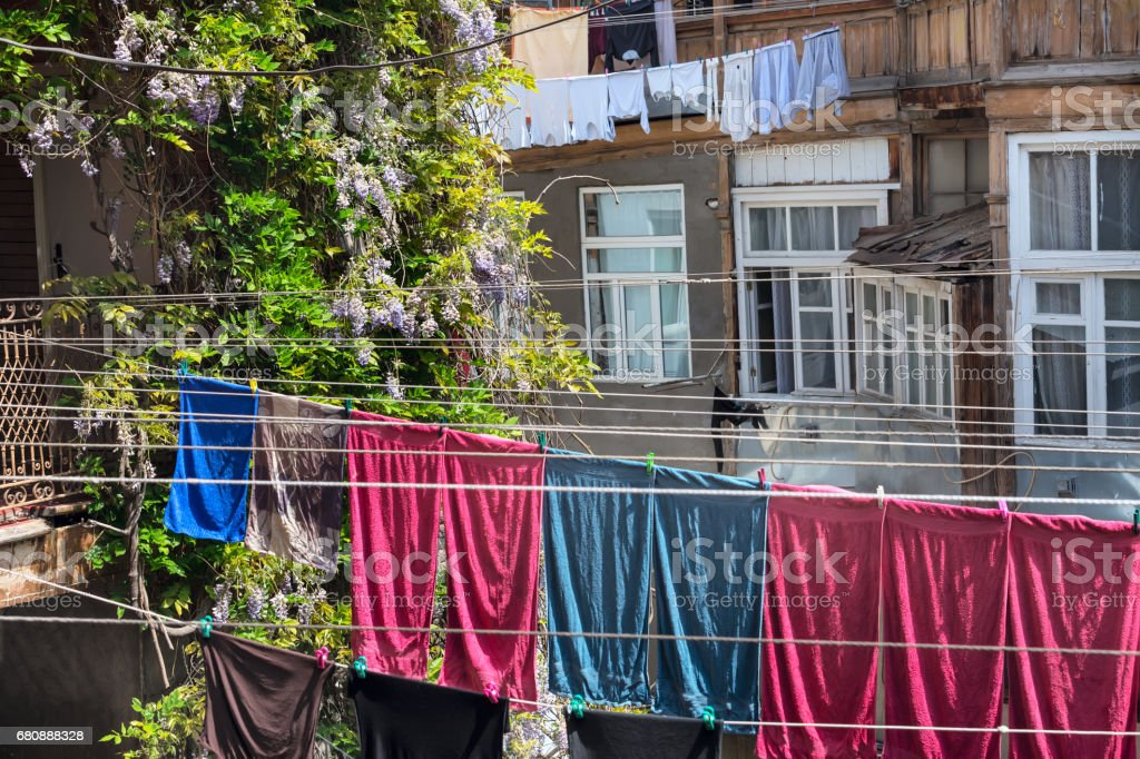 typical georgian yard of old traditional wooden house with flowers, clothes and linen drying on the ropes, Tbilisi Georgia stock photo