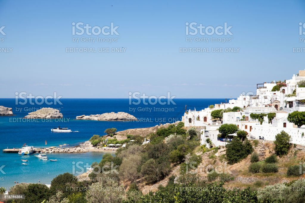 Typical Greek architecture. White houses on the coast. Fragment of the town lidos under acropolis. View of the harbor and bay. Blue sea lagoon and ships. stock photo