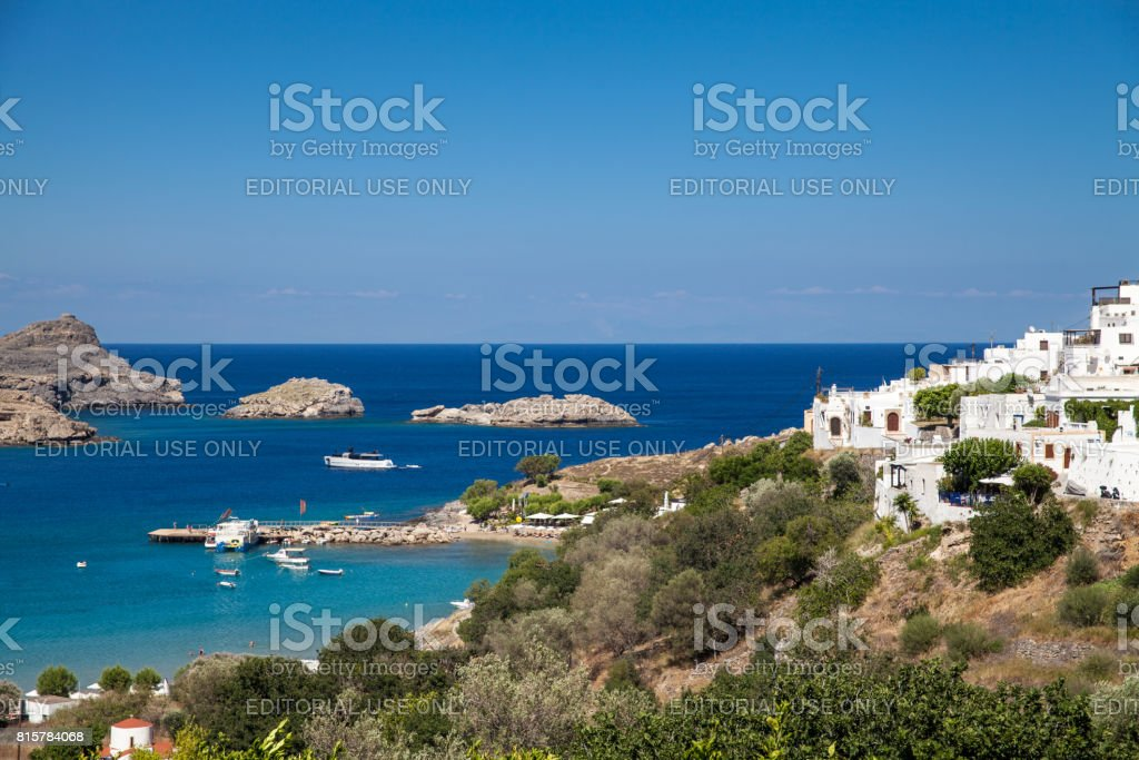Typical Greek architecture. White houses on the coast.Fragment of the town lidos under acropolis. View of the harbor and bay. Blue sea lagoon and ships. stock photo