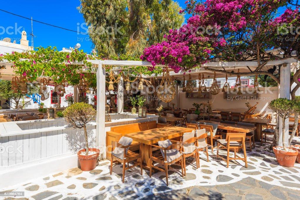 Typical Greek small restaurant on street in beautiful Mykonos town, Cyclades islands, Greece stock photo