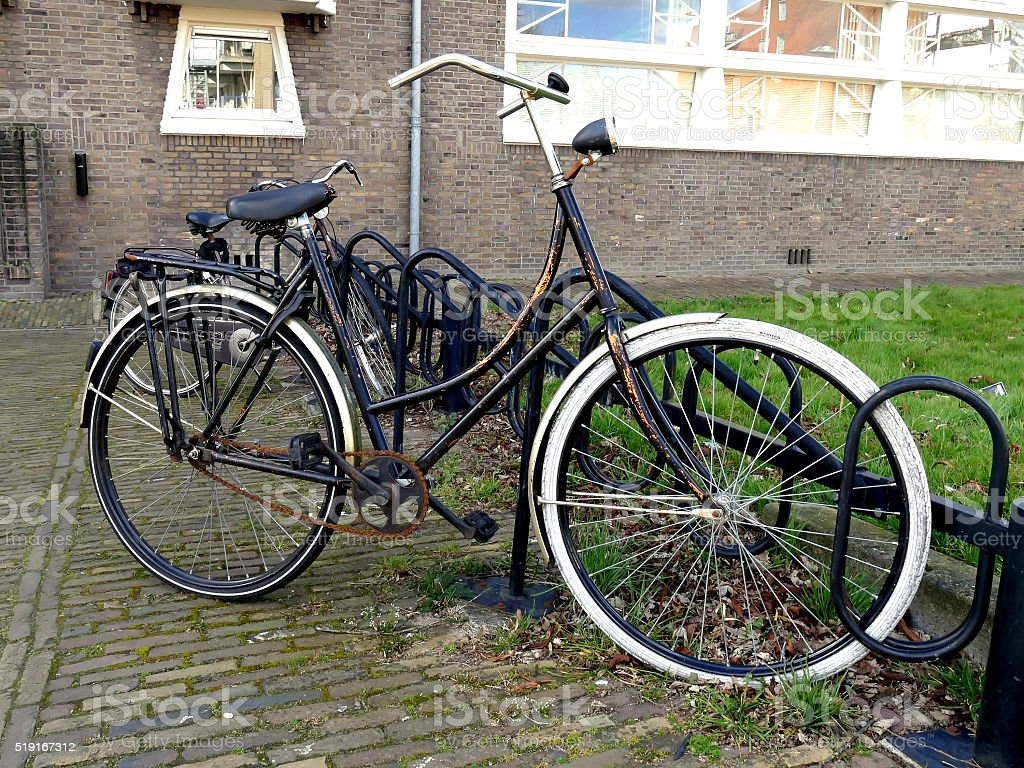 Typical old Dutch bike in bicycle rack or bicycle stand stock photo