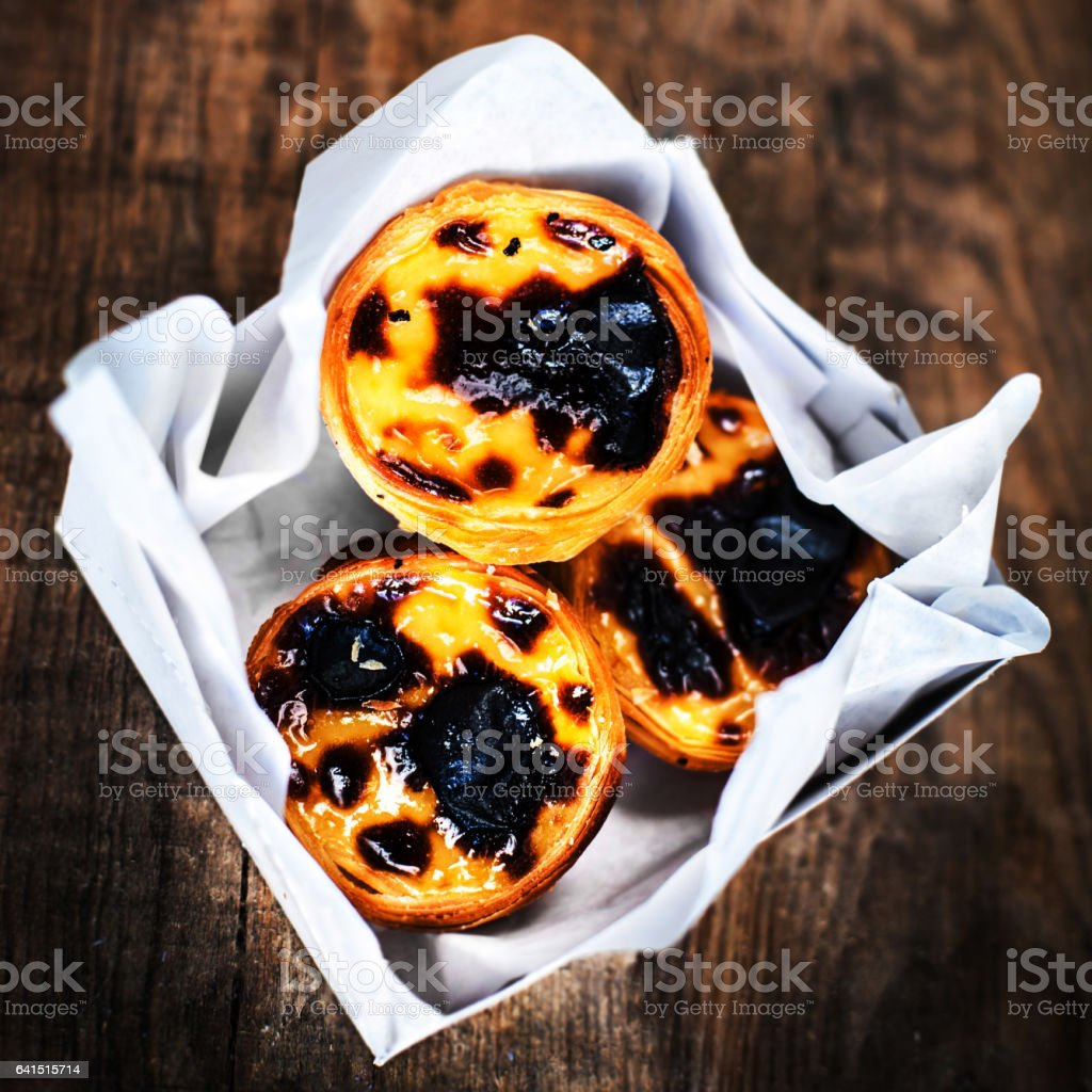Typical portuguese dessert pasteis de nata in a white box on wooden background with copyspace  / Heap of egg tarts stock photo