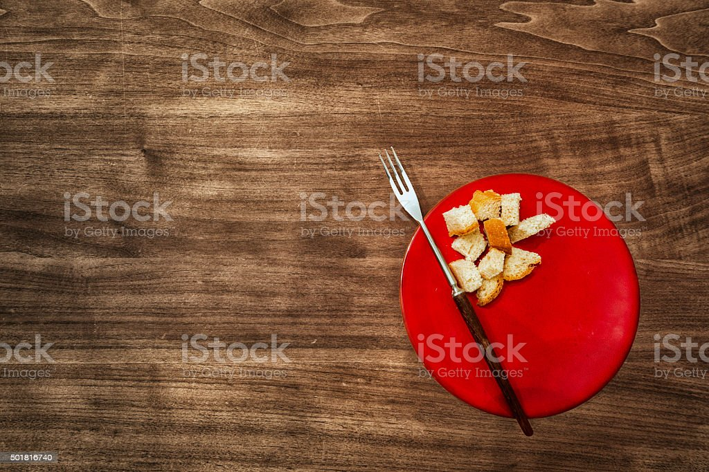 typical red fondue plate and fork on walnut wood table stock photo