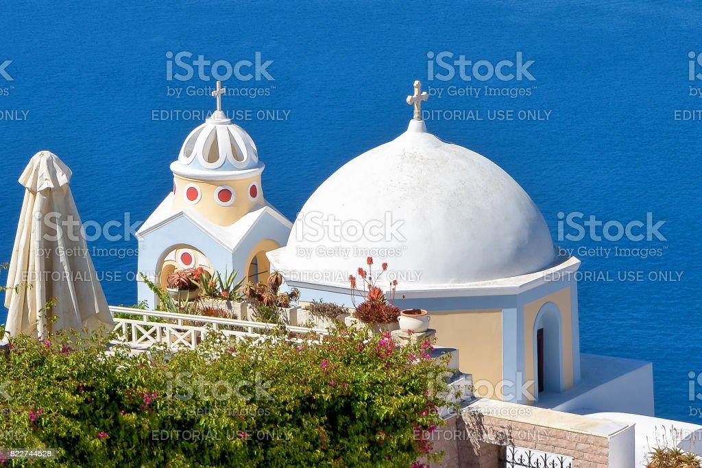 Typical Santorini island church domes with blue Aegean sea background stock photo